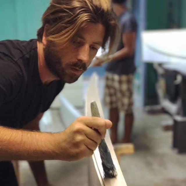 Alessandro Grande mentre rifinisce una tavola da surf personalizzata