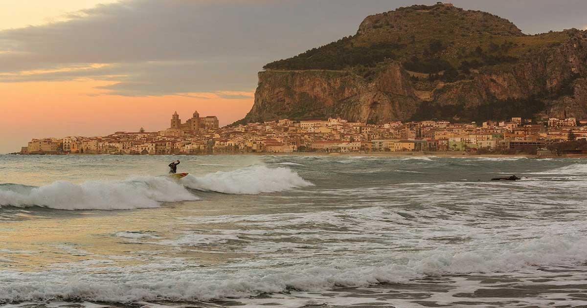 Un surfista durante il sunset a cefalù