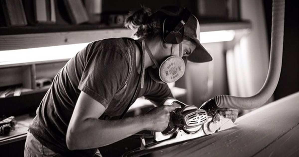 shaper donna mentre crea una tavola da surf a mano