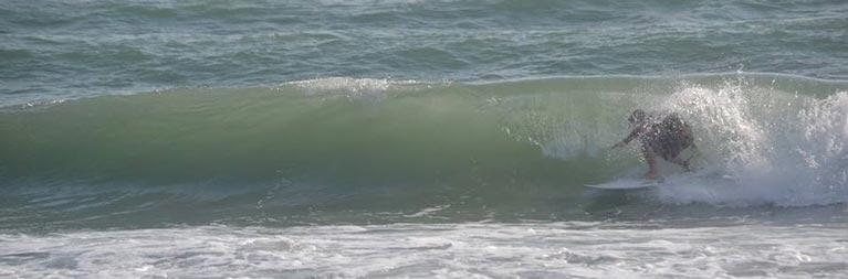 Un surfista all'interno di un piccolo tubo. Sulle coste laziali con le condizioni meteo e la tavola giusta il divertimento è assicurato