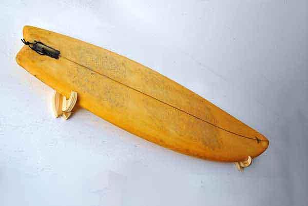 una tavola da surf appesa al muro con il supporto minimal, leggero e di design