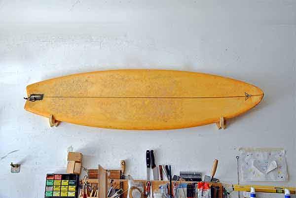 Una tavola da surf appesa al muro del laboratorio di SURF4HOME con il supporto minimal, leggero e di design! Disponibile su Blide.zone