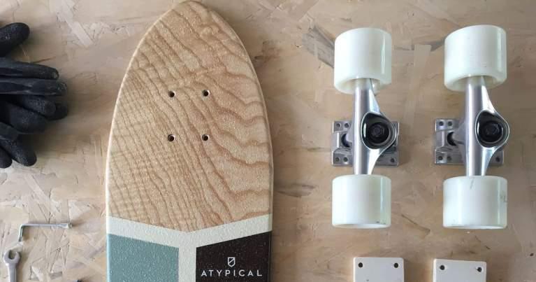 una tavola da skate con i truck e riser pad creata da Atypical, un'artigiano di Blide che produce tavole skate in legno massello