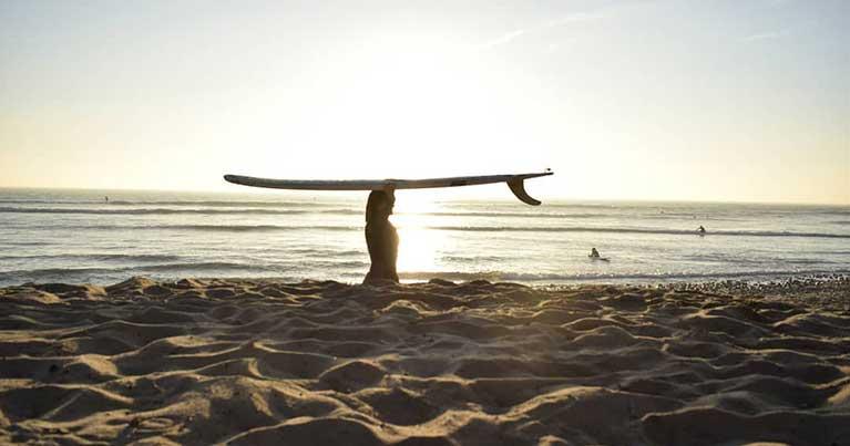 Cinzia con una tavola da surf e una delle sue mute su misura. In un intervista si racconta su Blide.zone, trucchi e storia del neoprene per il surf