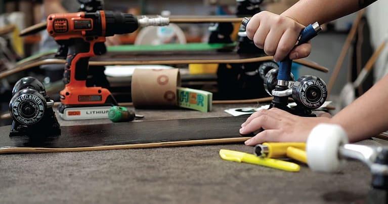 skater che si prende cura della tavola da skate e dei truck e delle ruote