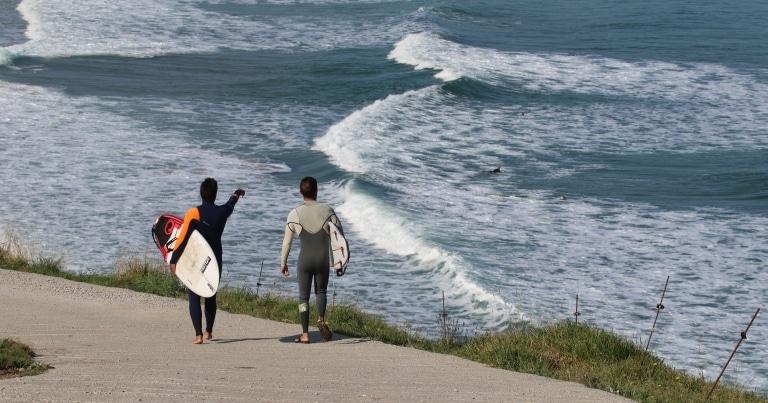 Michele con un'amico con già le loro tavole da surf, che osservano la line up durante una bella mareggiata portoghese