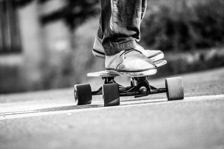 il dettaglio di un rider mentre gira sul suo longboard personalizzato per le strade cittadine
