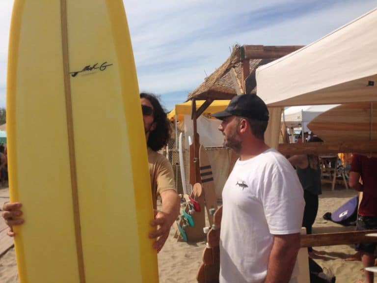 uno shaper itliano mentre mostra la sua creazione ad un surfista