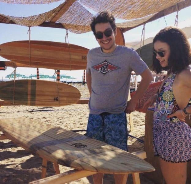 Due surfisti che osservano una tavola da surf in legno interamente realizzata a mano