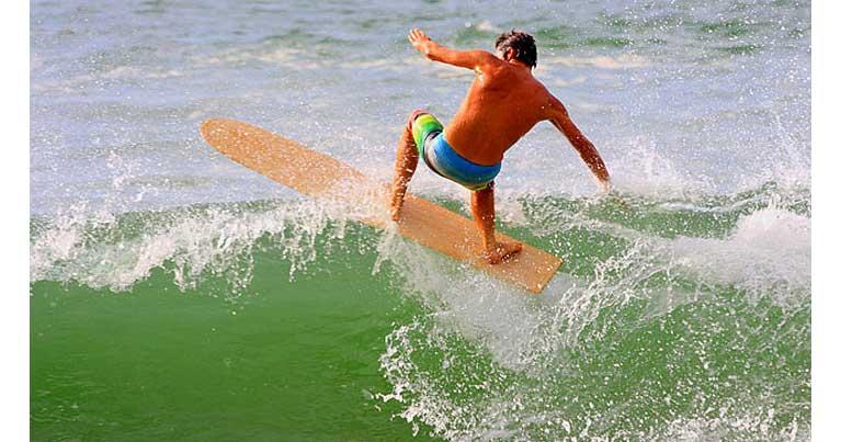 surfista mentre surf con alaia la tavola da surf in legno per eccelenza